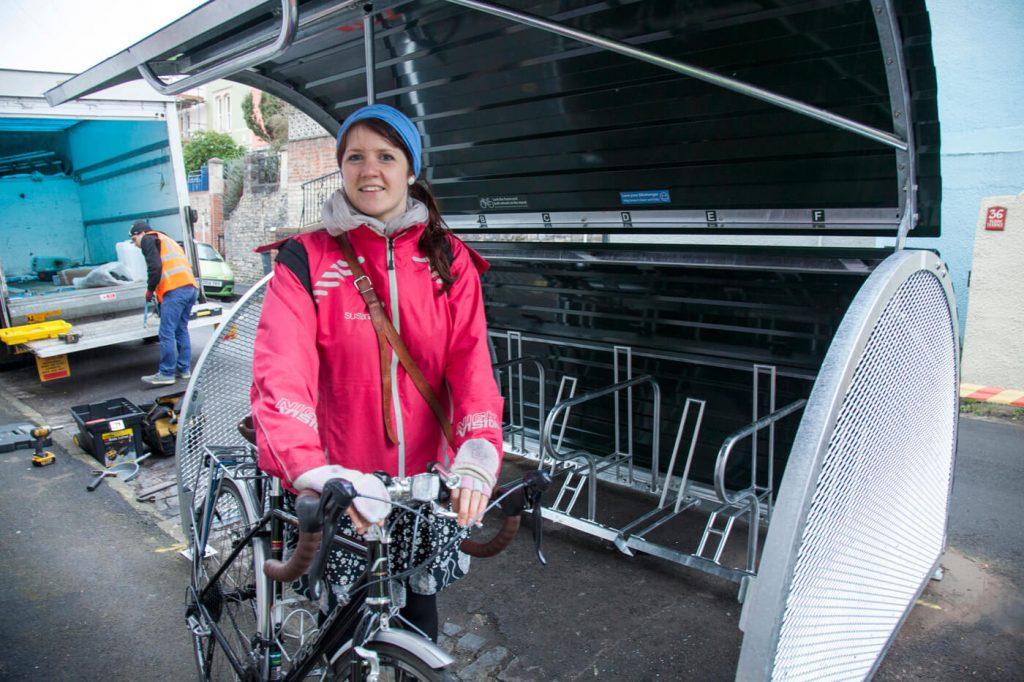 Woman standing near an open bike hangar holding a bike