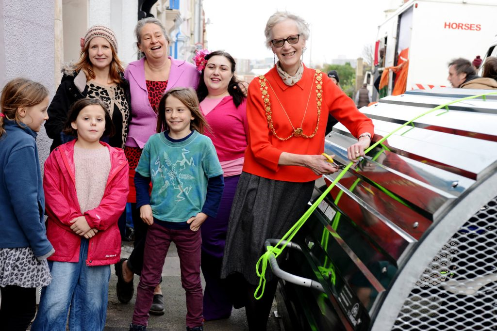 Group of people standing near the Bristol Mayor as she cuts the ribbon on the bike hangar