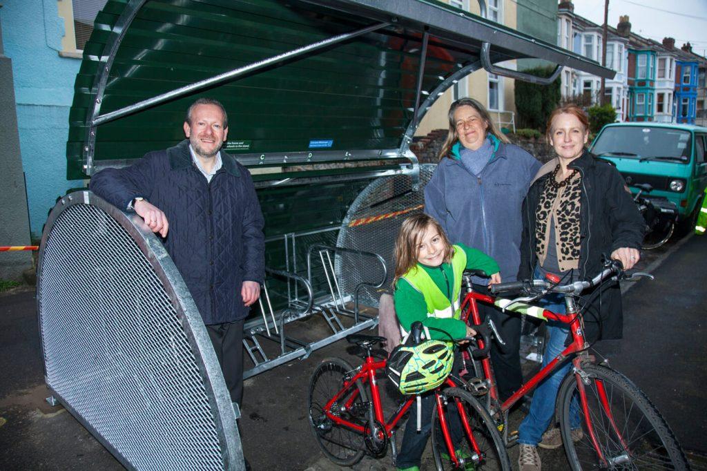 People near a bike hangar holding bikes