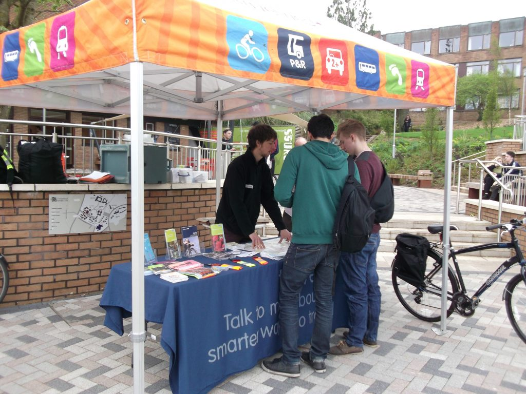 A group of people talking with a roadshow team member at a Travelwest stall