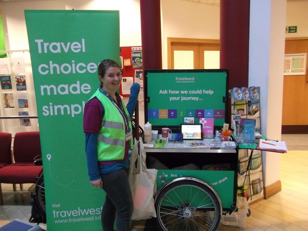 Woman standing near a Travelwest roadshow sign which reads Travel choices made simple. Ask how we could help your journey...