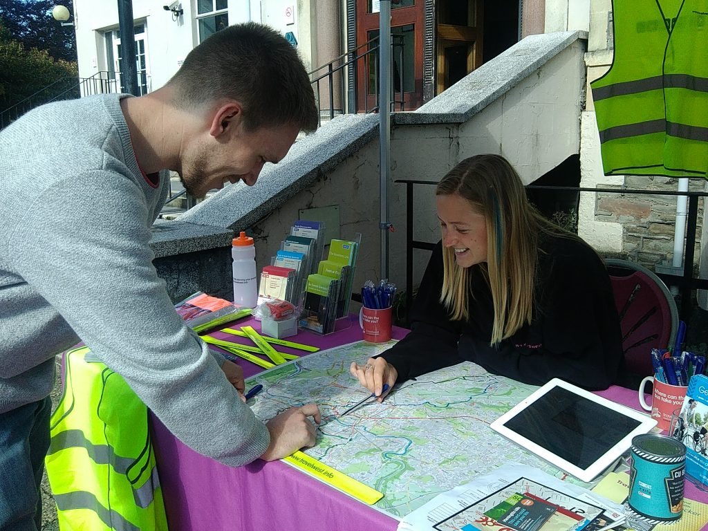 People smiling whilst looking at a map