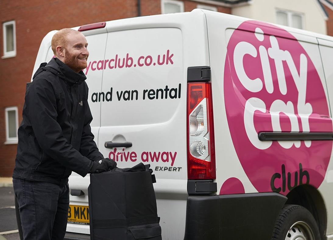 Man standing next to a city car club van