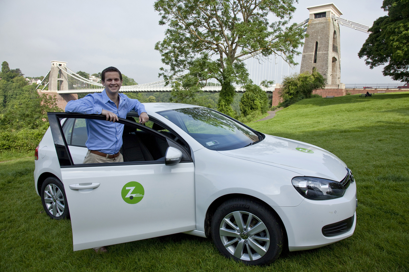 Man standing next to a zipcar vehicle with the door open with the Bristol suspension bridge in the background