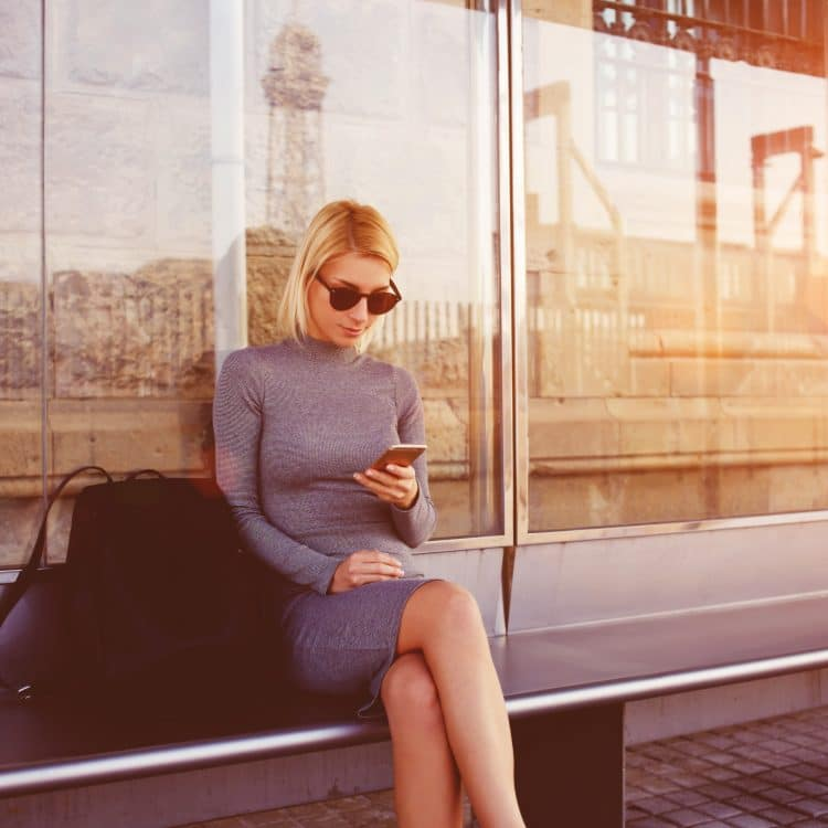 woman sitting at bus stop looking at her phone