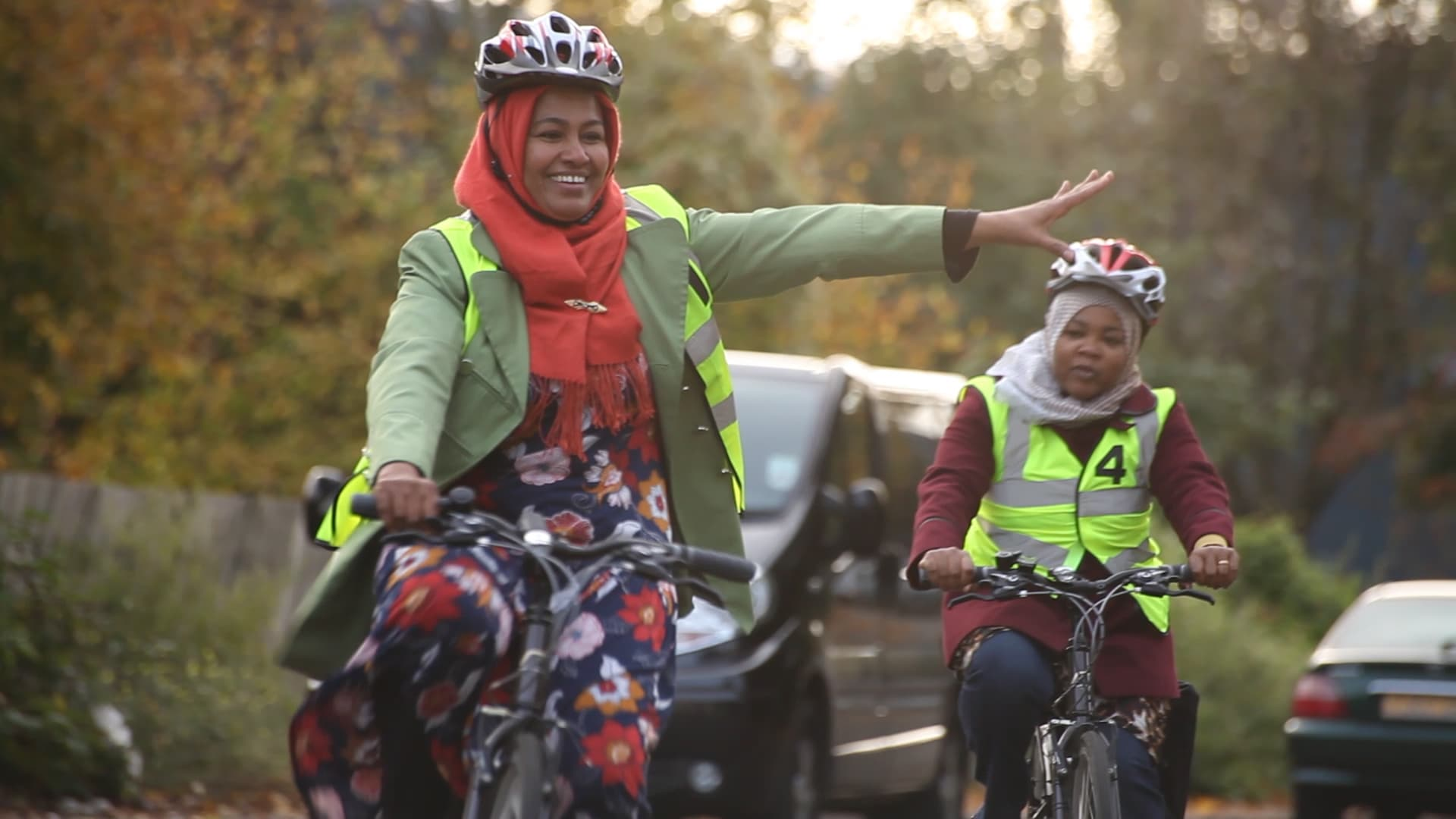 Two women cycling on a road. One woman is smiling and signalling that she's turning to the left by stretching her arm out to her left.