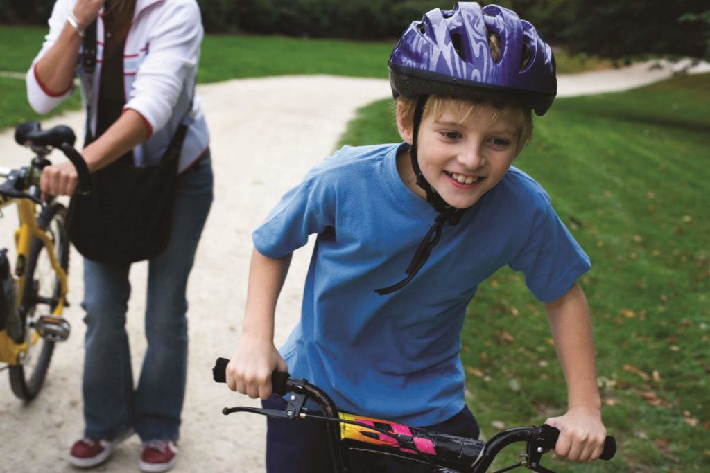 Young boy riding a bike on a park path