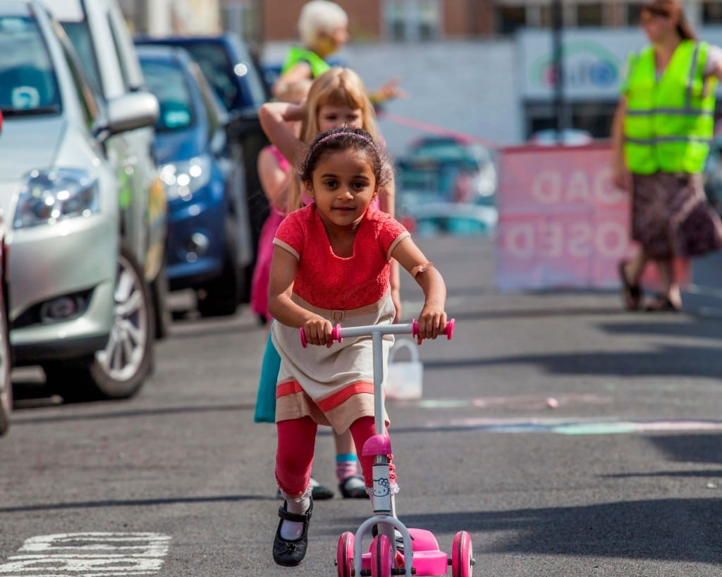 Little girl scooting on a closed road.