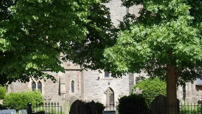 Photo of a stone building with a cemetery in front of it. There are big leafy trees in front of most of the building.