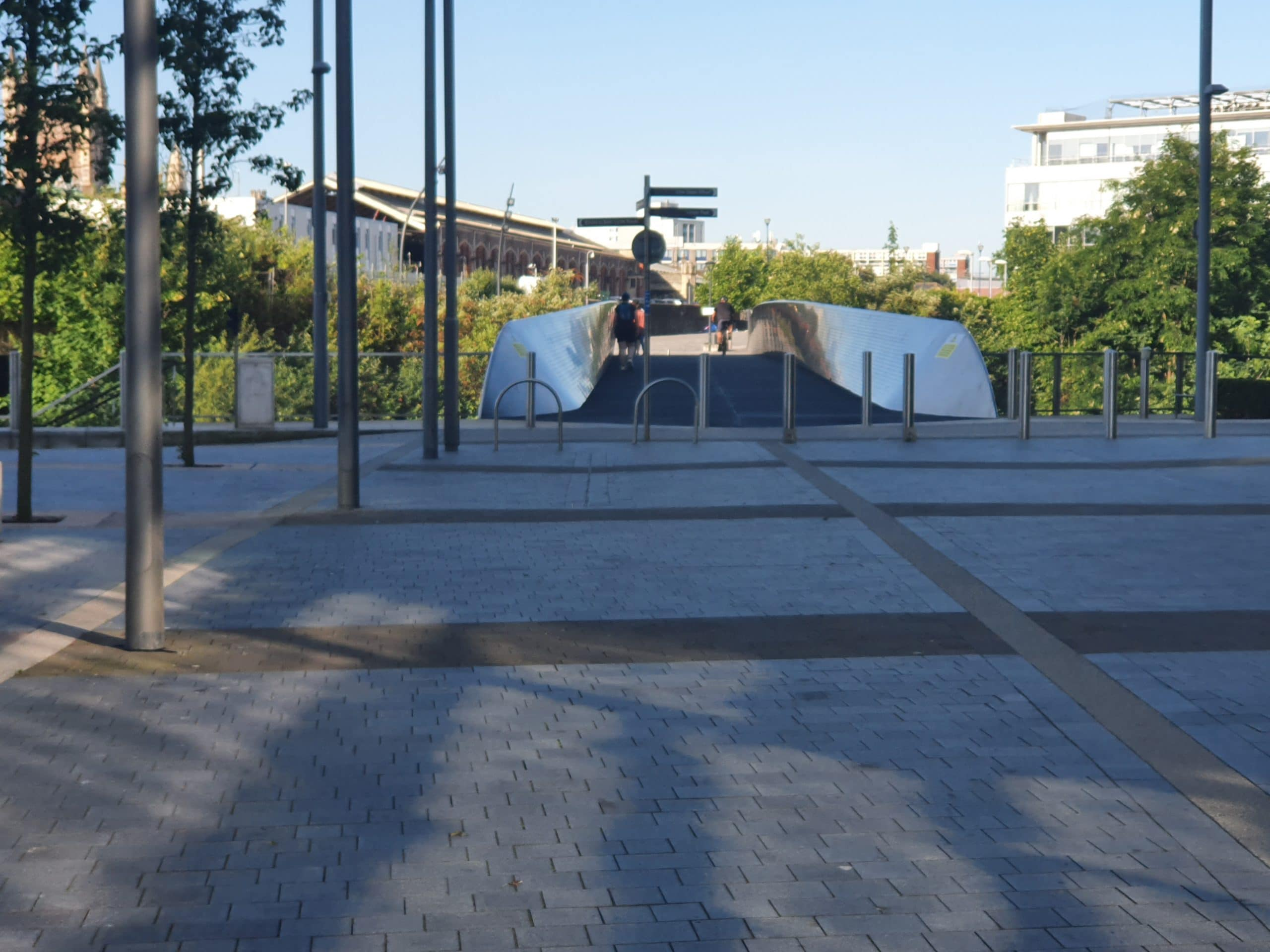 Photo of shared path metal bridge with people walking and cycling over it. There are some bollards at the entrance, and cycle parking. Some pedestrian traffic signs at the entrance are pointing in different directions. There are big green trees on the ground under the bridge and we can see Bristol Temple Meads station in the background.