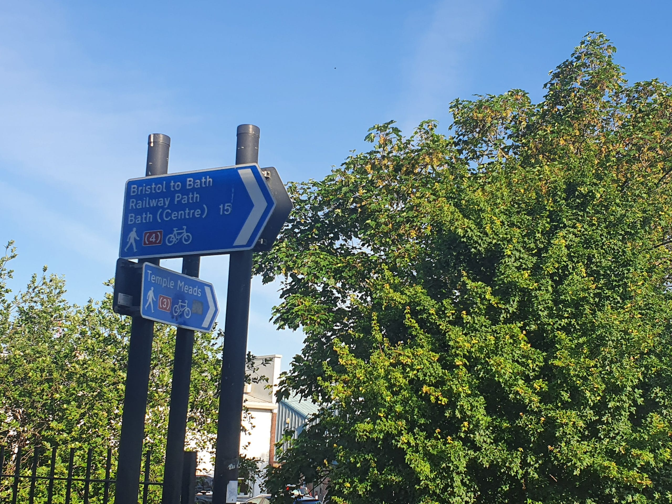 Photo of pedestrians and cyclist traffic signs showing: Bristol to Bath Railway Path; Bath (Centre) 15; Temple Meads. There are big trees next to the signs.