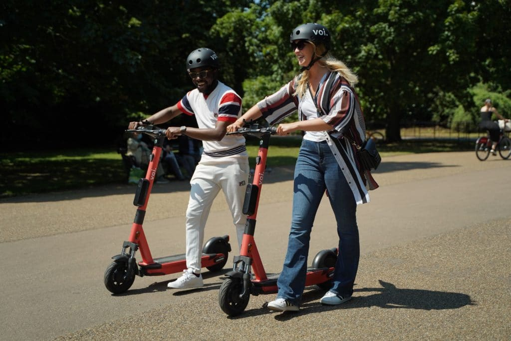 Man and woman walking on path whilst pushing e-scooters next to them
