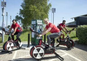 Three people on gym bikes, surrounding a new revive charge point.