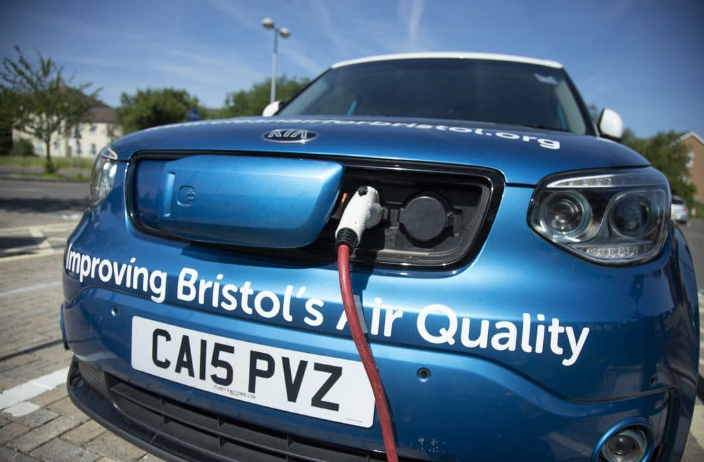 """A blue Kia plugged in to a charging point's cable. A phrase on the car reads """"Improving Bristol's Air Quality"""""""