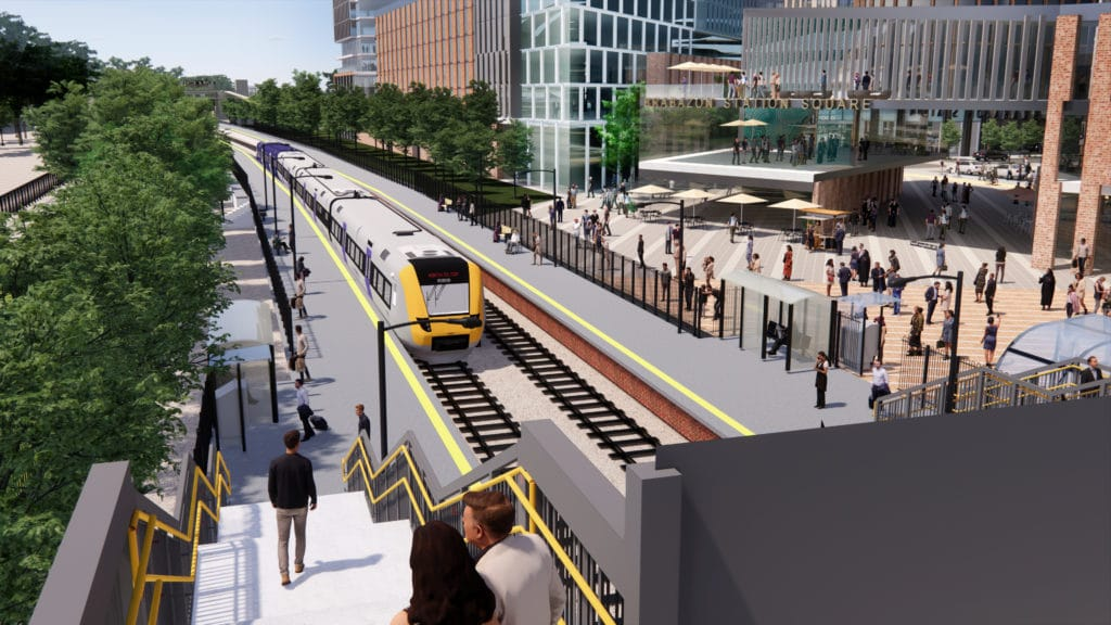 """Artist illustration of aerial view of station, from top of footbridge. There's a train arriving which reads """"North Filton"""", and people waiting on both platforms. There are people going up and down the stairs to the footbridge. In the background there is a square and tall buildings with big windows, a lot of people walking around outside and a sign that reads """"Brabazon Station Square"""". There are a lot of big trees lining the sides outside the tracks."""
