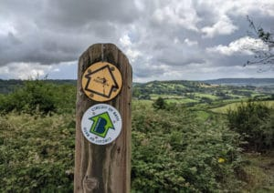 Close up of directions wooden post in rural area with signs for public footpath and circuit of Bath, Bathscapes.